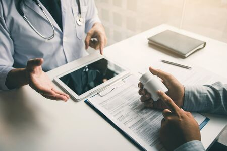 Asian doctor talking the patient at clinic while using the tablet explaining the patient condition and the treatment result.