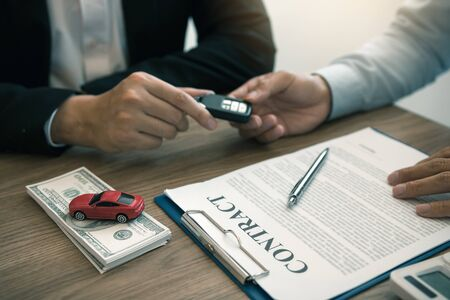 New car buyers enter the car keys and sign the contract documents in the showroom of the car salesmans office.