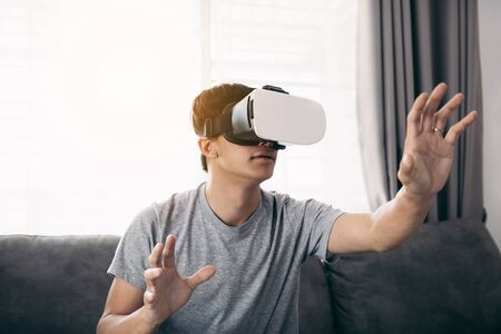 Young asian man wearing virtual reality glasses at living room for admiring virtual reality.