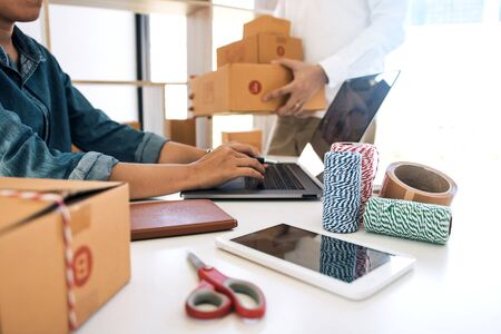Two business owner are working together to pack products and check customers orders on their laptops at home. Stockfoto