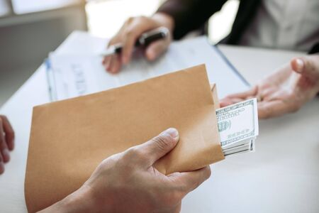 Businessman secretly giving a bribe by giving money bills in envelope contract document. Stock Photo
