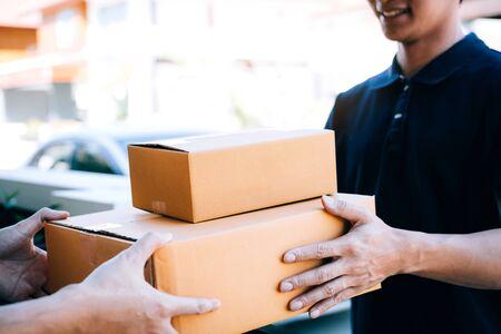 Le transporteur de fret asiatique tient une boîte en carton avec le colis à l'intérieur et le destinataire signe le colis.