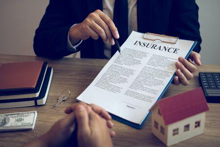 Gli agenti usano penne che indicano contratti assicurativi e vengono spiegati ai clienti in ufficio.
