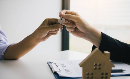 Hand of real estate agent passes the key to new homeowners in office with buyer house concept. Imagens