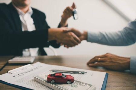 Neuwagenkäufer und Autoverkäufer schütteln sich die Hände, um Vereinbarungen über den Autoverkauf zu treffen. Standard-Bild