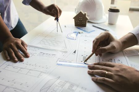 Architect working on blueprint discussing new project with colleague in office.