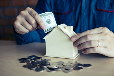 Men are using banknotes in the home piggy bank with the idea of collecting money to buy a new house. Zdjęcie Seryjne