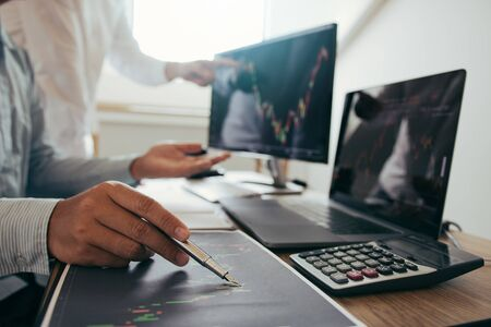 Close up of pen investors are working together with analyzing the stock data graphs in the paper and viewing the data on the laptop screen. Zdjęcie Seryjne