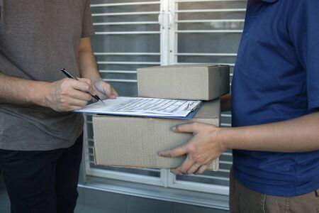Delivery young man standing at the door of home and carrying parcels for young male to signing.