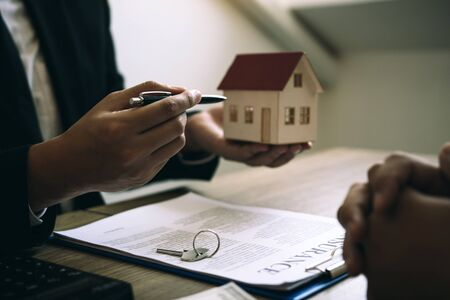 Business people home sales broker is using a pen pointing to the house model and describing the various components of the house. Stock Photo