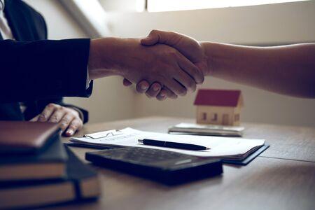 Hausverkäufer und Käufer arbeiten daran, neue Häuser zu unterzeichnen und Hände zu schütteln.