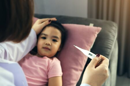 Asian female pediatrician is using a thermometer to measure fever for children