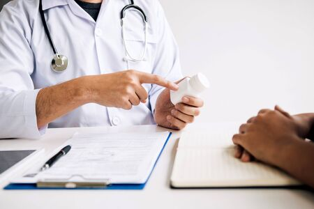 Confident doctor man holding a pill bottle and writing while talking with senior patient and reviewing his medication at office room. 版權商用圖片 - 145858295