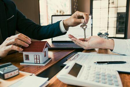 Salesman house brokers provide key to new homeowners in office. 写真素材