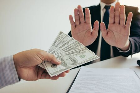 Business person refusing bribe given money by partner with anti bribery corruption concept.