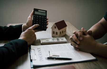 Agents are calculating the loan payment rate or the amount of insurance premiums for customers coming to contact the purchase of a new home at the office. Reklamní fotografie