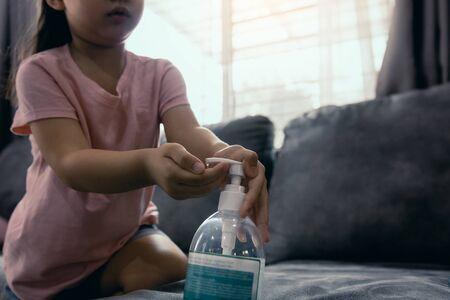 Asian girl kid using wash hand sanitizer alcohol gel pump dispenser in house during the coronavirus outbreak. 写真素材