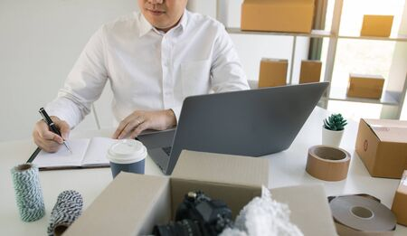 Young asian man looking on computer laptop and taking writing order list on paper with business owner concept.