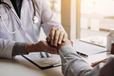 Doctor is holding the patient's hand and giving hope about treating the symptoms of the disease.