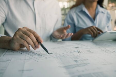 Architects engineer working with blueprints on table and discussing project together at the meeting in the office. Banco de Imagens