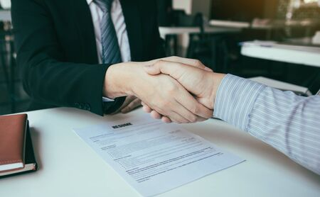 Manager and employee interview concept with handshake after talking about contract signing.
