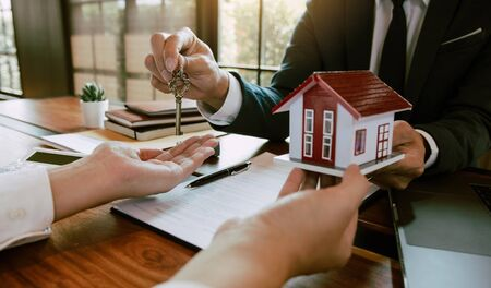 Home agents are handing out keys to home buyers who are signing contracts at the office. Фото со стока
