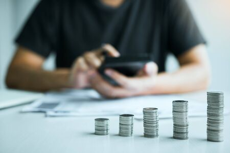 Asian men are calculating about finances about the cost or future investment at home while the coins are arranged with the idea of saving.