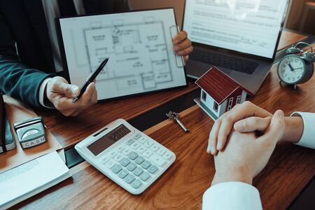 Agents are using pens pointing to blueprint home design and are being explained to customers at the office. Stock fotó