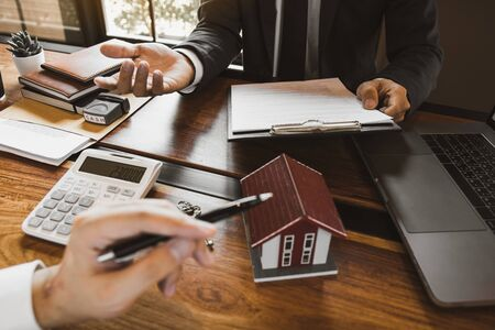 Business people home sales broker is using a pen pointing to the house model and describing the various components of the house. Reklamní fotografie