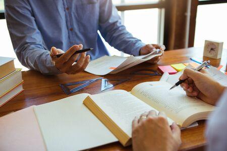 Teenager studying at desk and doing homeworks Standard-Bild