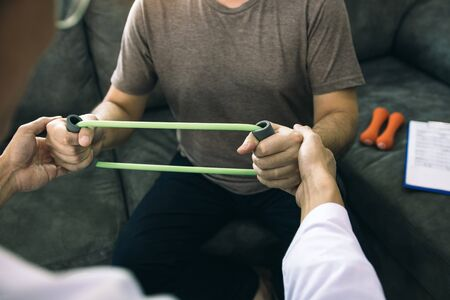Asian male physical therapist descent working and helping to protect the hands of patients with patient doing stretching exercise with a flexible exercise band in clinic room. Standard-Bild