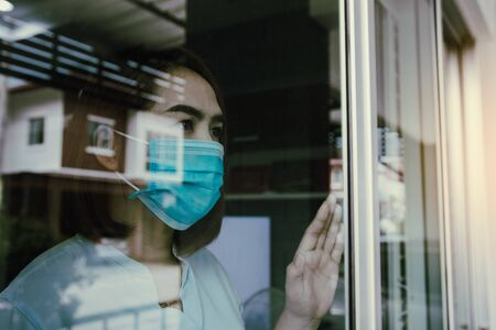 Asian woman looking through the window and wearing medical mask protection from the illness with stay isolated quarantine COVID-19 pandemic virus mask against coronavirus disease at home. Standard-Bild - 149939099