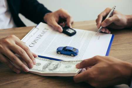 New car buyers are signing a contract with a car salesman at the showroom on the day of receiving the car and handing cash to the employee.