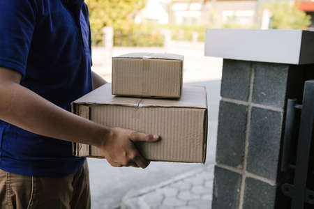 Asian cargo carrier holds a cardboard box with the package inside and the recipient is signing the package.