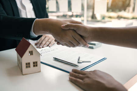 Home sales agents and buyers work on signing new homes and shaking hands. Standard-Bild