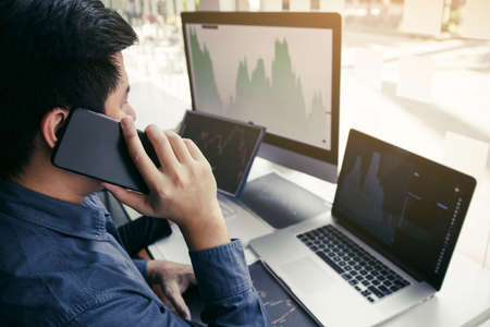 Two asian agent man working and analysis together in office  market financial charts and graphs and calling to customer. Standard-Bild