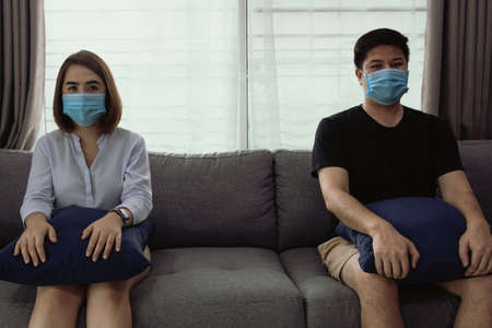 Two asian couple lovers sit on the sofa at home spaced apart from social distancing concept in a new strain of virus epidemics with coronavirus Covid-19. Standard-Bild