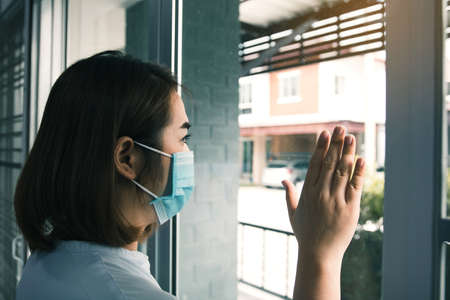 Asian woman looking through the window and wearing medical mask protection from the illness with stay isolated quarantine COVID-19 pandemic virus mask against coronavirus disease at home.