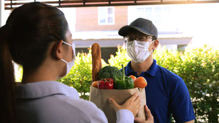 Delivery of an asian man handing a bag of food to a female customer at the door while wearing a protective mask during a virus epidemic. Standard-Bild