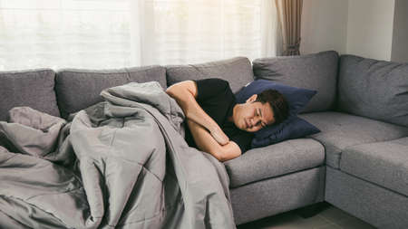 Asian people are sick or ill with bronchitis while coughing by covering their mouth with tissue paper when he sit on the sofa at home.