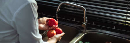 Asian hands woman washing vegetables tomato and preparation healthy food in kitchen. Standard-Bild