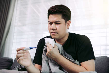 Asian people feel stressed because having cough and cold and using a thermometer to check if he has fever or illness at his home. Standard-Bild