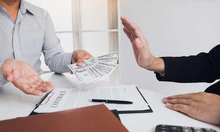 Businessperson refusing bribe given money by partner with anti bribery corruption concept. Standard-Bild