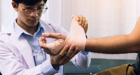 Asian physiotherapists are examining the results of wrist surgery of patients.