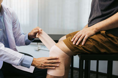 Asian physiotherapists are examining the results of knee surgery.