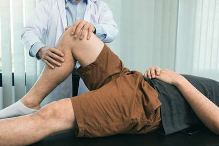 Physical therapists are using the handle to the patient knee to check for pain.