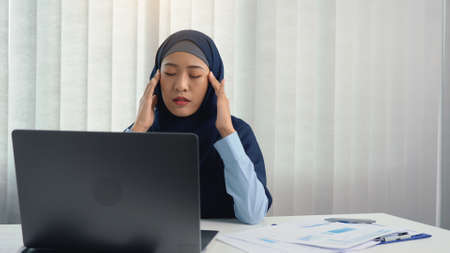 Muslim woman kneaded her head with a hand massage while suffering from a migraine headache.