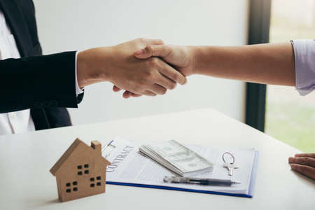 Home sales agents and buyers work on signing new homes and shaking hands. Фото со стока