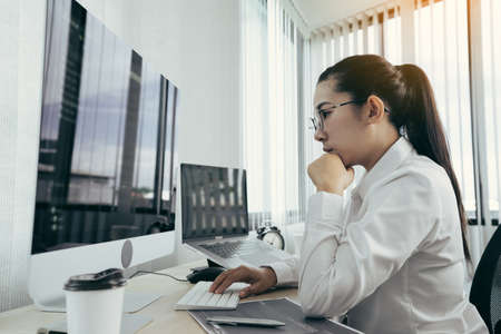 Asian female software developer is worried about analyzing code-based systems at his office.