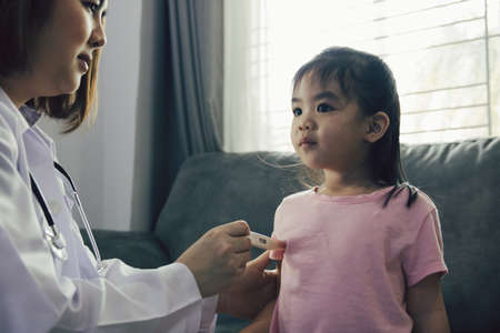 Asian female doctor is using a thermometer to measure the fever for the children at his home.